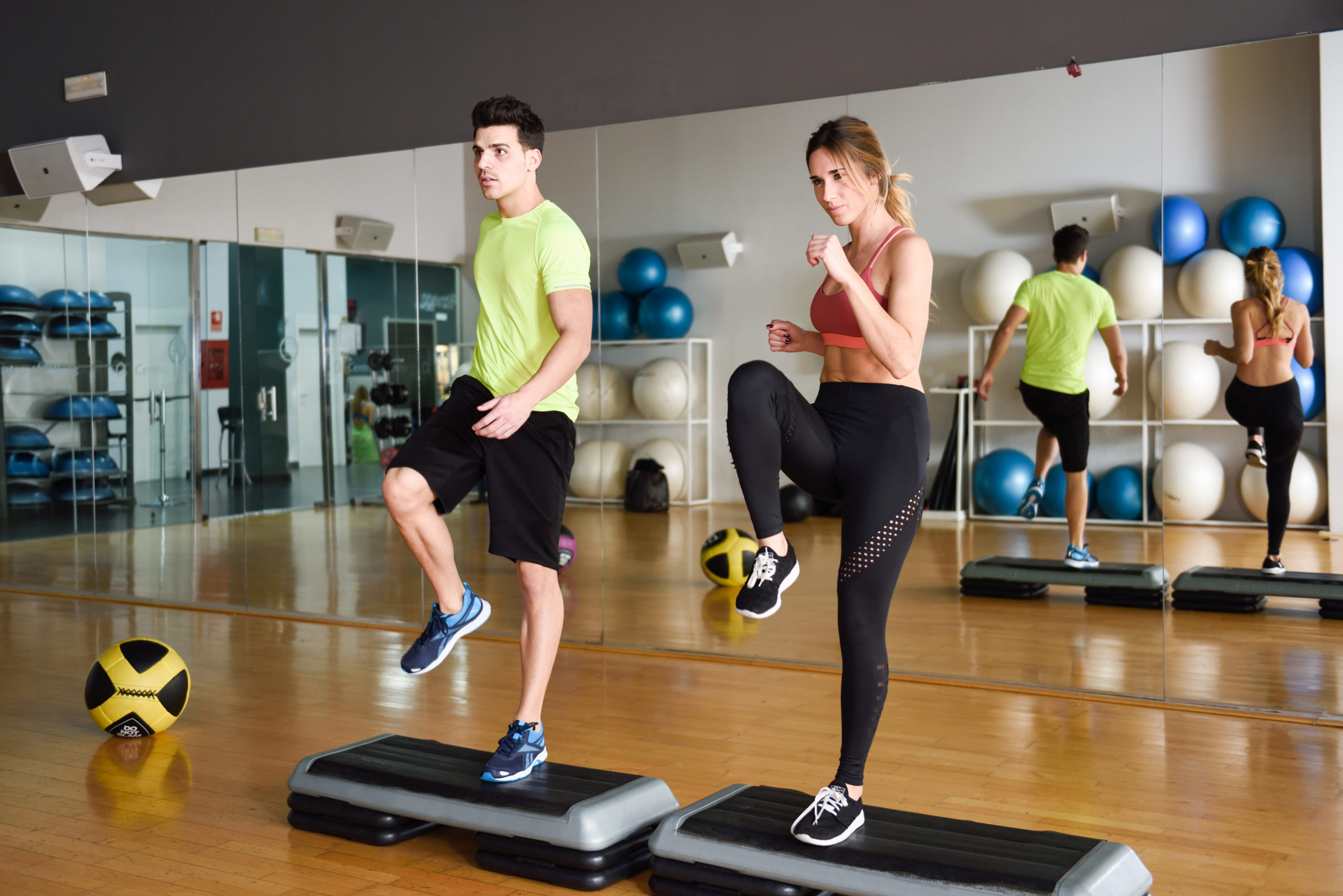 Two people working out with steppers in gym. Man and woman wearing sportswear clothes.