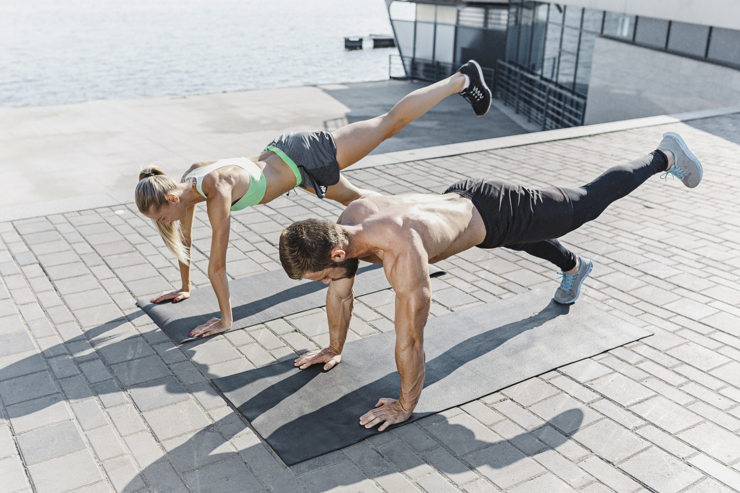 Fit fitness woman and man doing fitness exercises outdoor at city background. the best abdominal muscle press in the world. Female and male sports models exercising in summer at morning.